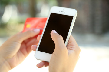 Cellphone and credit card in woman's hands outdoors, close up