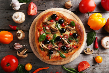 Delicious heart shaped pizza with vegetables on wooden background, close up