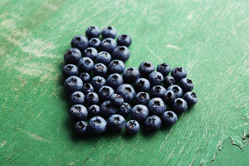 Heart shaped bilberries on old wooden background