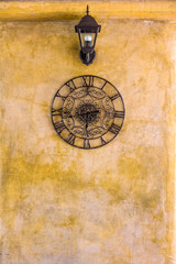 Vintage hanging  clock and lamp on old wall. Retro decoration for interior design.