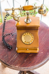 Vintage landline telephone on wooden table. It is a rotary dial phone.