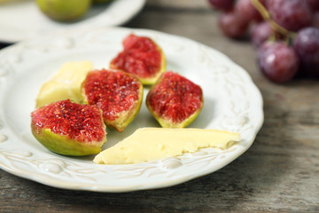 Ripe figs and cheese on plate, on wooden background