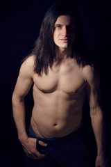 handsome young man with long hair naked torso on black
