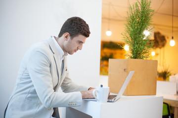 Man using laptop in white office