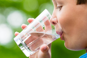 Boy drinking fresh water from glass
