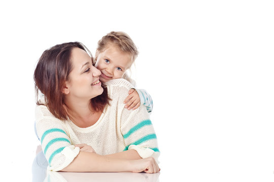 Mother are playing with daughter in studio, white background