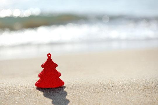 red christmas tree on sand beach
