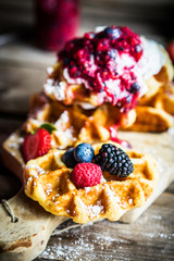 Belgian waffles with fresh berries on rustic wooden background