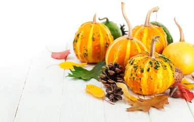 Autumnal pumpkins with yellow leaves on wooden board