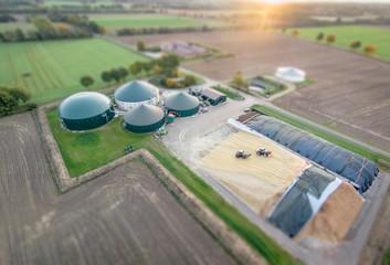 Luftbild - Miniatureffekt, Traktoren walzen Maissilage für Biogasanlage fest