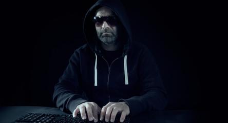 Night hacker typing on keyboard