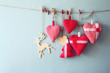 christmas image of fabric red hearts and tree, wooden reindeer, hanging on rope in front of blue wooden background. retro filtered