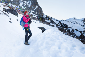 Wall Mural - Backpacker woman standing snow mountain trail.
