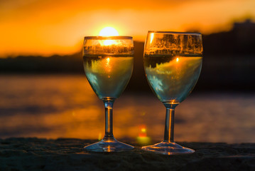 Two wine glasses on the background of sunset seascape
