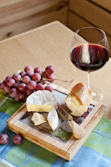 Glass of wine with cheese and grapes on the table