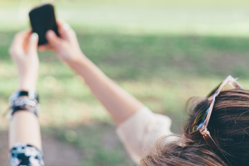 Closeup of girls taking self-portrait in the park with copy spac
