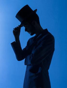 Silueta de un mago con chistera en azul