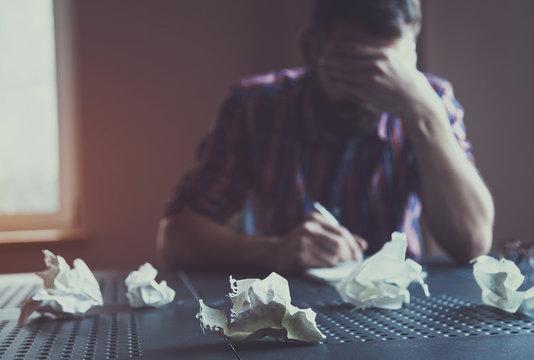 Paper balls during bearded man writing