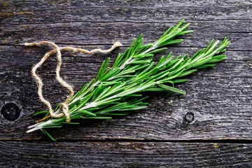Fresh rosemary springs on wooden background