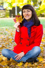 Smiling woman in autumnal park holding colorful leaves in hands