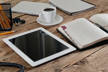 tablet computer with a notebook for notes and cup coffee