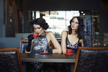 Two girls are sitting in a cafe and drink coffee.