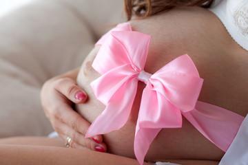 беременный животик с розовой лентой