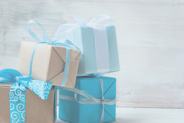 boxes with gifts decorated with ribbons on a white wooden backgr