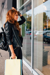 Girl with shopping bags looking at something in a shop window