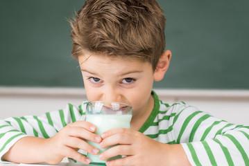 kind trinkt milch in der schule