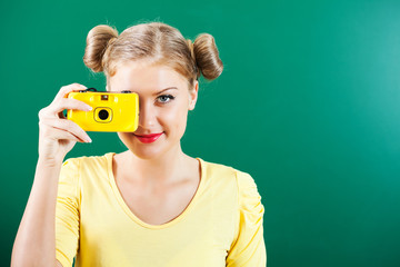 Happy student girl holding photo camera in front of blackboard