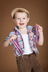 Stylish kid in studio, brown background