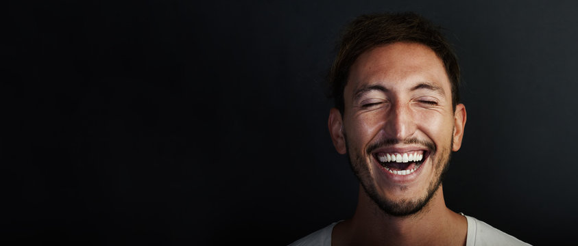 Portrait of cute young man wearing white tshirt and laughing  a lot. Wide