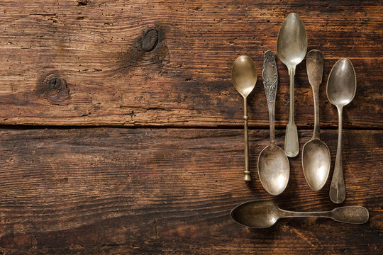 Metal spoons on wooden table