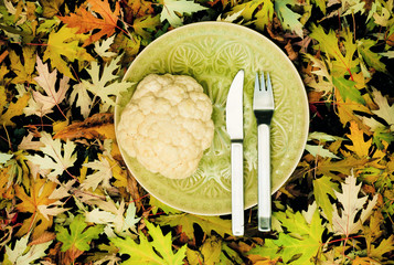 Cauliflower on a plate in the autumn background with leaves of yellowed trees