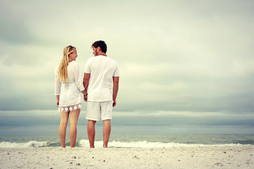 A happy young married couple is holding hands and looking at each other as the stand on a white sand beach looking out over the ocean while on vacation.