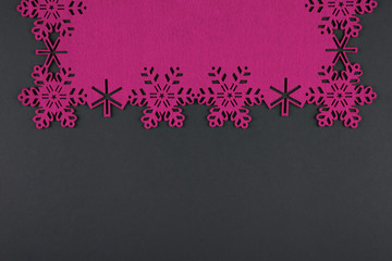 Unusual design christmas background with pink snowflakes and copy space on dark grey background