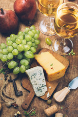 Cheese on wooden board and White wine, top view