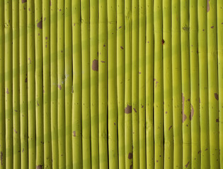 Stripe of shadow on yellow sprayed bamboo wall.