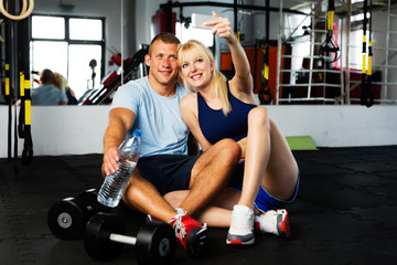 Young couple taking a selfie at gym