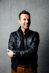 Happy man in leather jacket against concrete wall