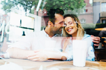 Happy couple hugging at cafe