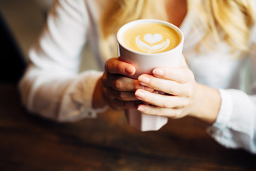 Closeup of woman holding warm latte