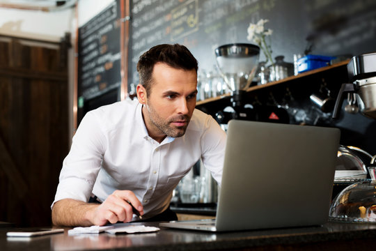 Restaurant manager working on laptop, counting small business income