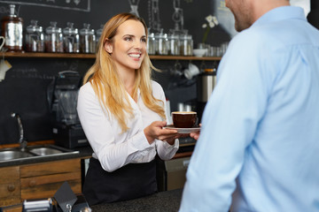 Pretty barista offering cup of coffee to restaurant client