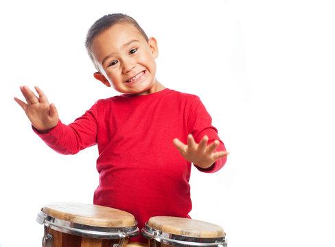portrait of a little boy playing bongos