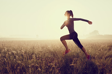 Young woman running during sunset Wall mural