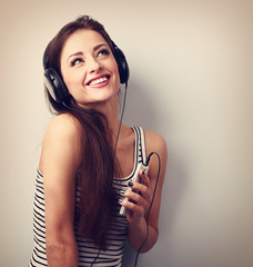 Pretty smiling girl listening the music wearing headphones holdi