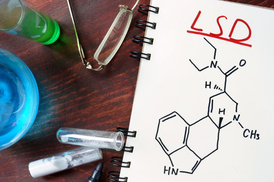 Notepad with chemical formula of LSD on the wooden table. Drugs concept.