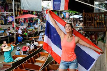 Joyful woman having fun at Damnoen Saduak floating market showing Thailand flag at Bangkok. Female tourist on Asia Travel.